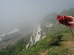 Small red knitted mouse held in front of the Cliffs of Dover