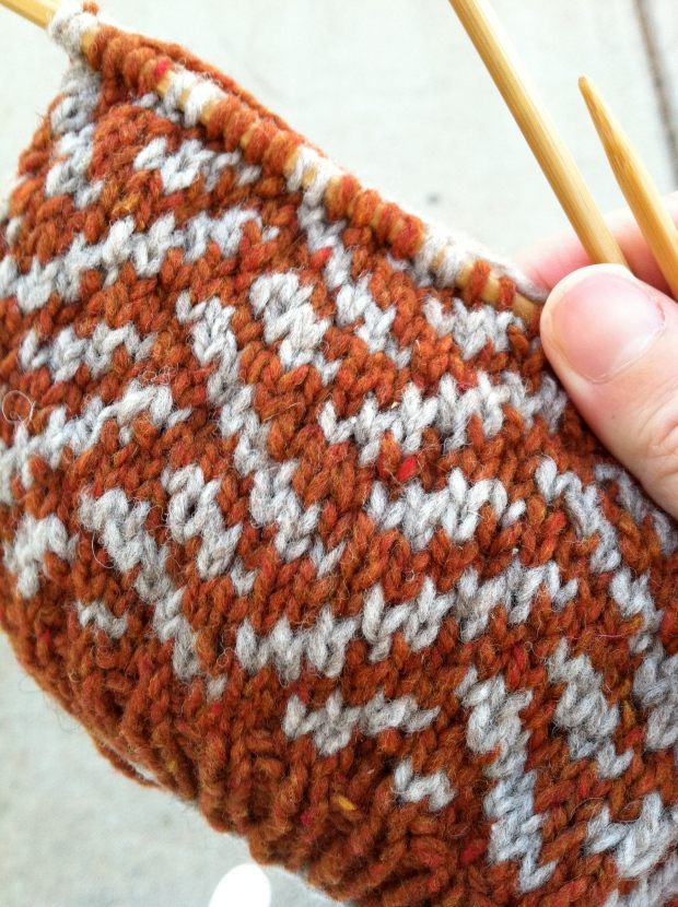 Orange and gray hat on knitting needles