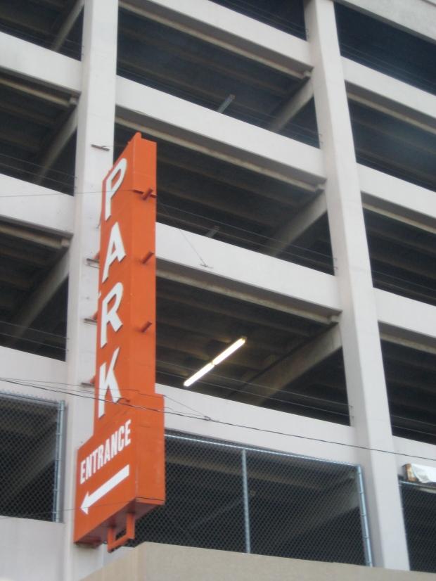 Orange park sign affixed to the side of a parking garage