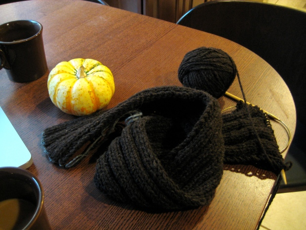 Strip of brown knitting on a table with a miniature pumpkin