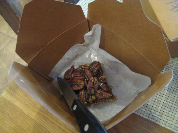 Pecan bar in a box with a knife