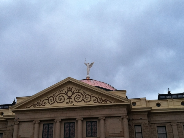 Marble statue of winged victory atop Arizona State Capitol seen against cloudy sky.