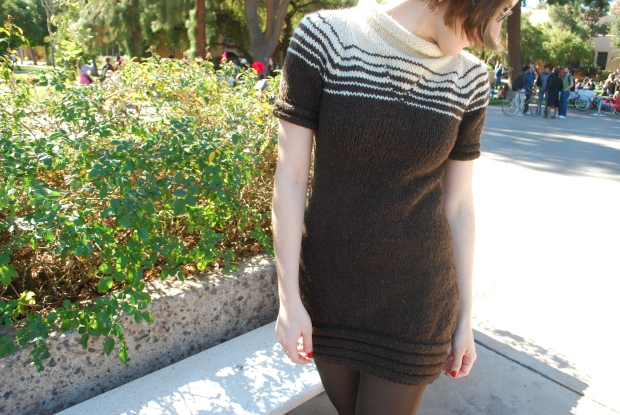 Girl wearing a knitted dress with a brown and white striped yoke