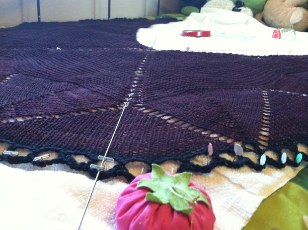 Purple and black knitted shawl blocking.
