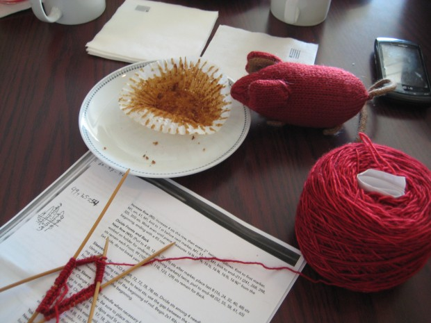 Knitted mouse on a table next to knitting and a muffin wrapper
