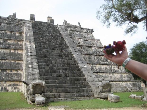 Knitted mouse and fabric frog in front of a pyramid at Chichen Itza