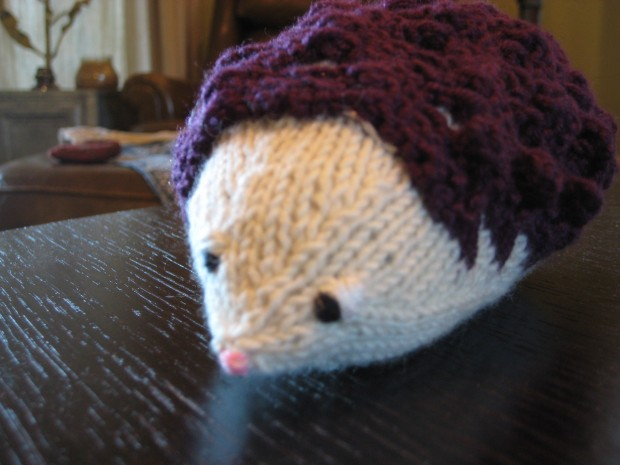 White knitted hedgehog with purple spines