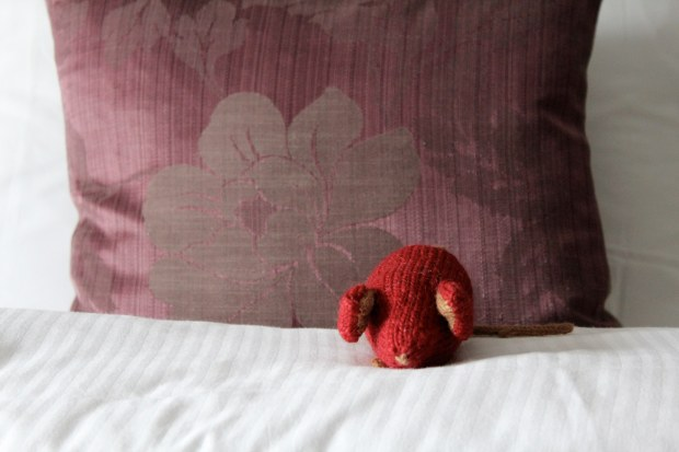 Red knitted mouse on a white duvet with a purple brocade pillow.