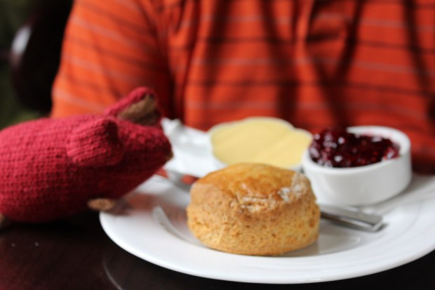 Red knitted mouse on the edge of a plate with a scone, butter, and jam.