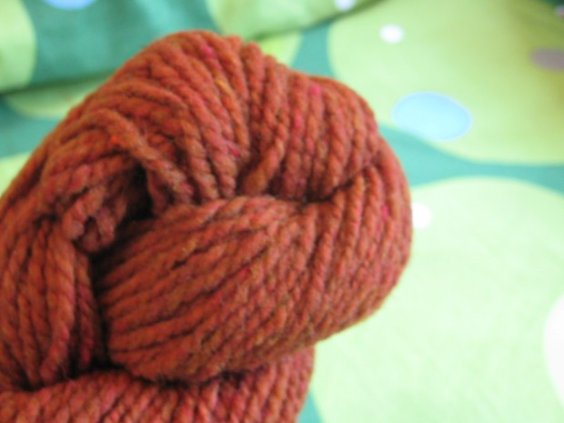 Skein of orange yarn against a green background