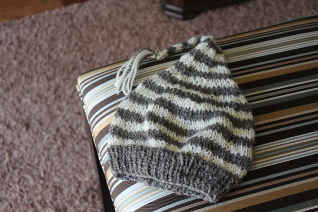 Grey and white striped knitted hat on a striped upholstered bench.