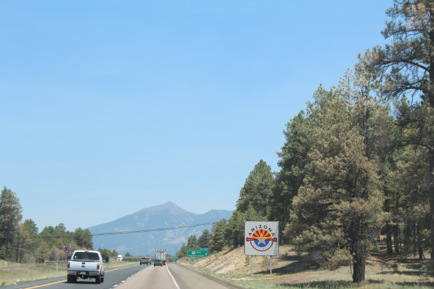 Trees along 1-17 south of Flagstaff, with an Arizona Centennial sign and Humphreys Peak in the distance.