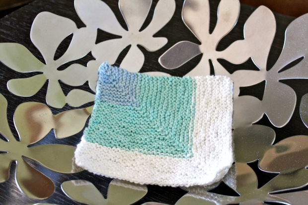 Blue, turquoise, and white washcloth in a silver bowl.