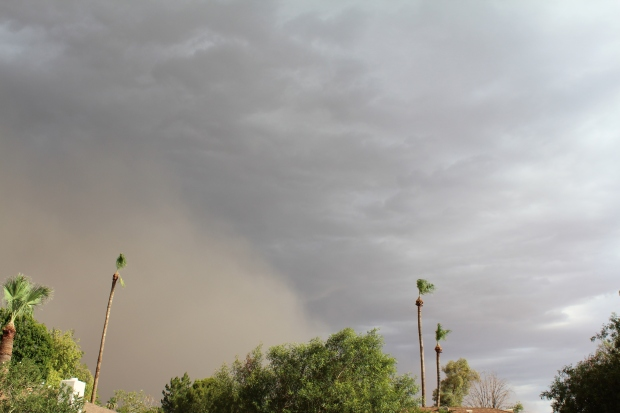 Brown dust storm blowing across cloudy sky