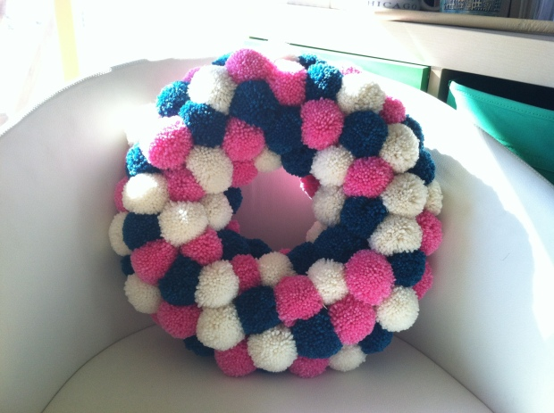 Wreath made of pink, white, and teal pom-poms