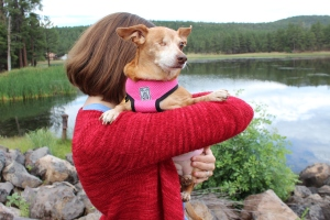 Girl carrying a smal dog.