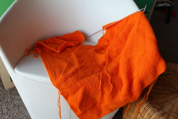 Knitted orange blanket on a white chair