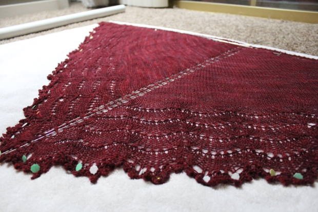 Burgundy shawl pinned out to block