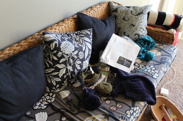 Wicker couch strewn with knitting