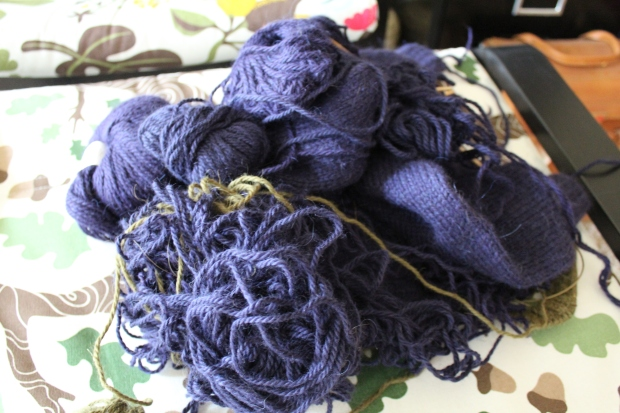 Partially unraveled purple and green sweater
