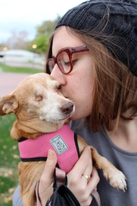 Girl kissing a small, one-eyed dog