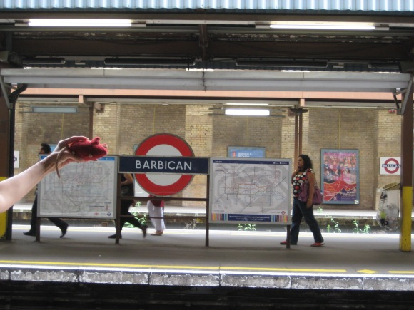 Red knitted mouse by the Barbican Tube sign