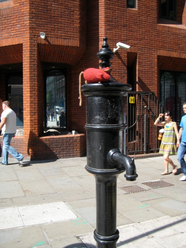 Red knitted mouse sitting on the Broad Street Pump