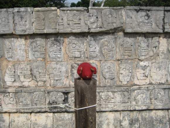 Red knitted mouse in front of the Xompantli in Chichen Itza