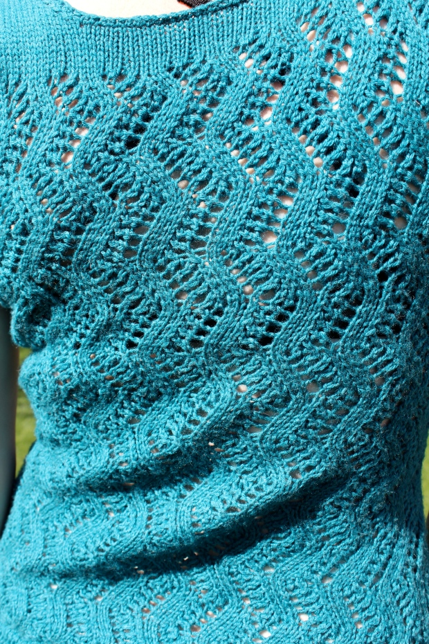 Detail of lace knitting on a teal tank top