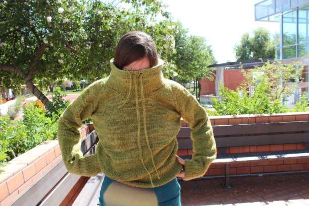 Girl putting on a green knitted sweater