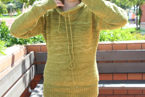 Girl putting on a green sweater