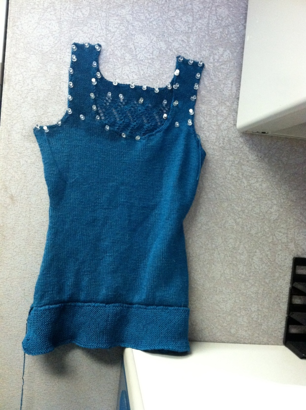 Teal tank top blocking while pinned to a cubicle wall