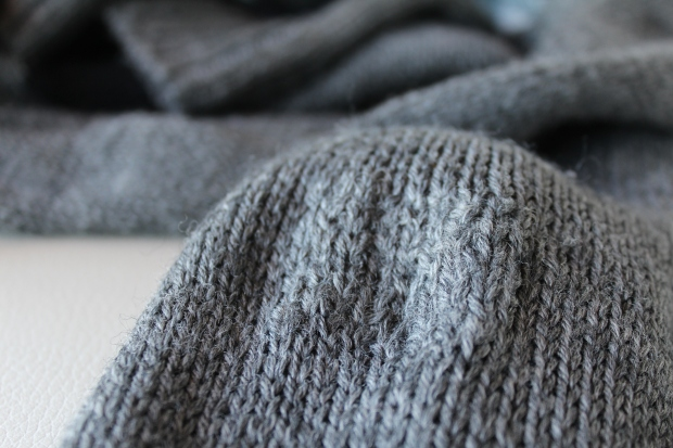Untidy darning on a gray sweater