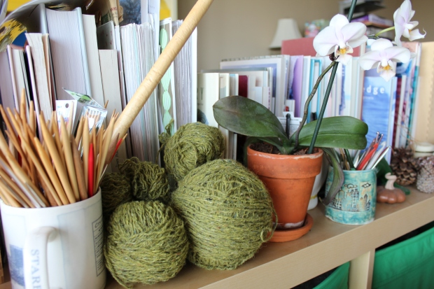 Balls of green yarn on a shelf with orchids