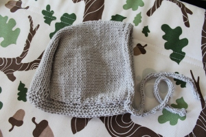 Gray baby bonnet on a brightly printed cushion
