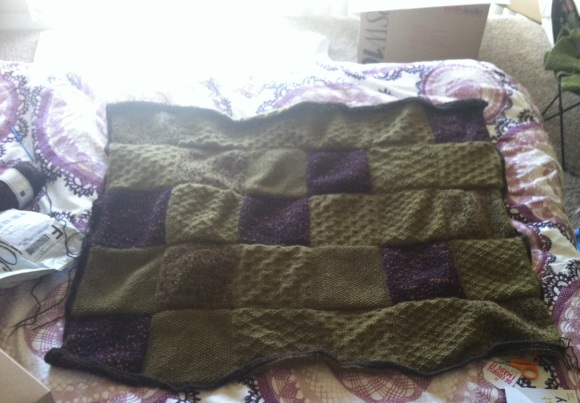 Knitted Patchwork Blanket spread out on a bed