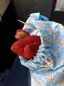 Red knitted mouse peeking its head out of a knitting bag