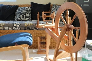 Spinning wheel, chair, and lazy Kate in front of a wicker couch