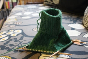 Dark green knitting on a sofa upholstered with Ikea fabric