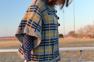Woman wearing a knitted plaid cape