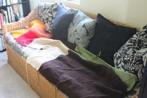 Patchwork garter stitch blanket on a wicker couch