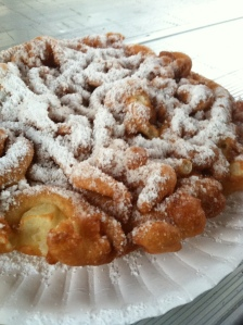 Funnel cake with powdered sugar on a paper plate