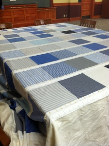 Blue and white quilt top spread out on a table