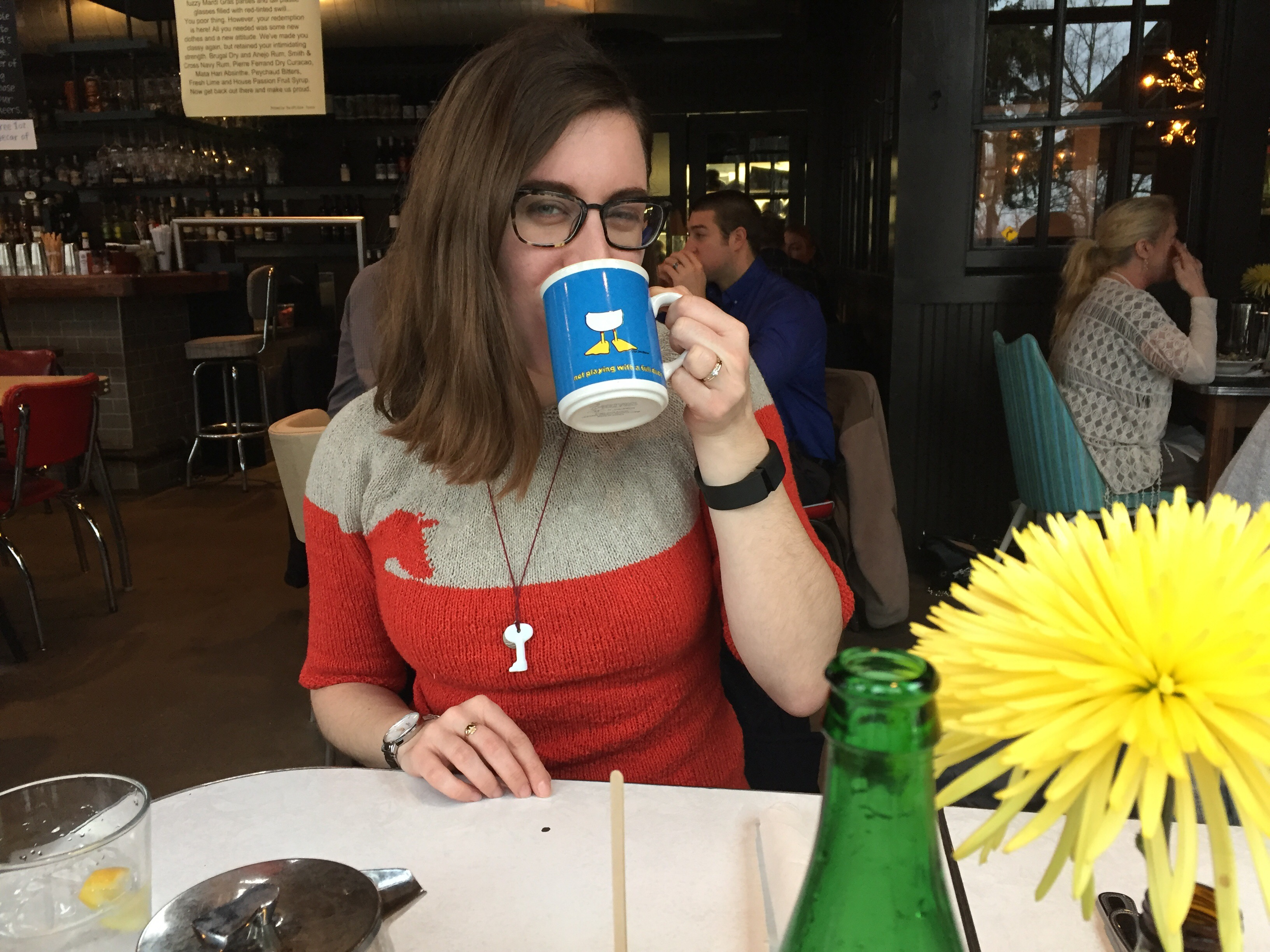 Woman wearing a Lonely Souls sweater and drinking a cup of coffee