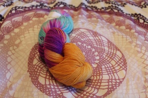 Nerd Girl Yarns fingering weight yarn in gold, turquoise, and fuschia