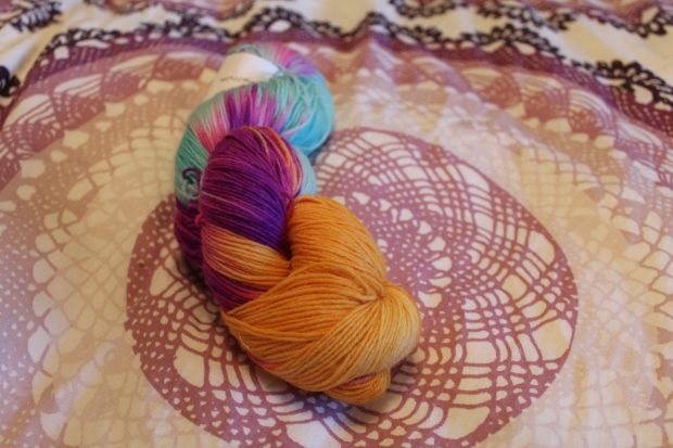Nerd Girl Yarns fingering weight yarn in gold, turquoise, and fuschia