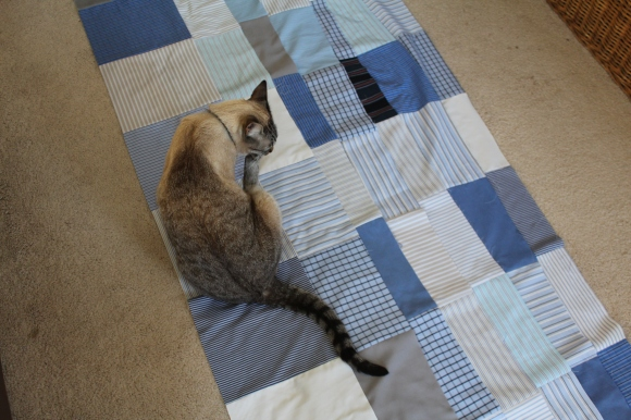 Cream colored cat cleaning her toes on a quilt in progress