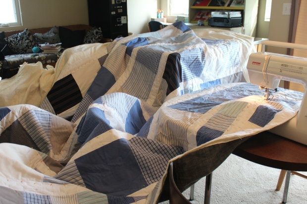Large blue and white quilt spread out across tables