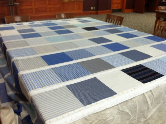 Blue and white quilt being sandwiched on tables