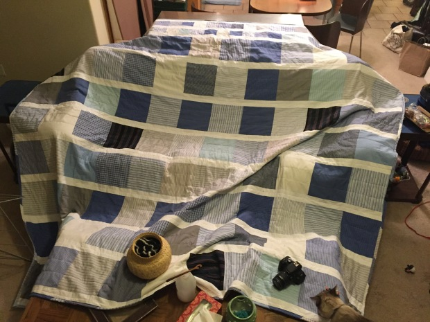 Large blue and white quilt spread out across a couch and two tables